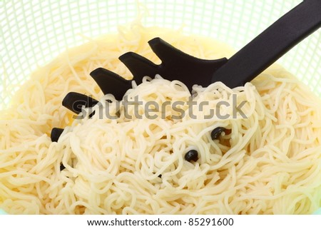 noodles in green colander isolated on a white background