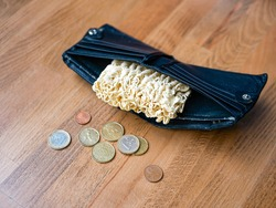 Noodles in the black leather wallet with euro cents. Instant noodle (ramen) in pocket and coins as poverty concept. No money in the business wallet. Bankruptcy, decrease, crisis. Financial problems.