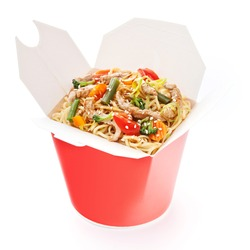 Noodles with pork and vegetables in take-out box on white background