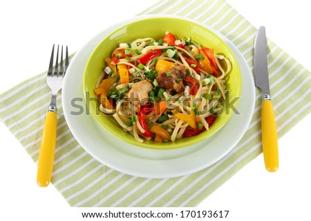 Noodles with vegetables on plate on napkin isolated on white