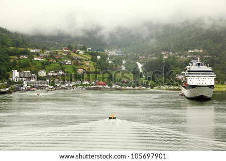 NORDDAL - JUNE 26: Cutter floats to shore with coastal village under mountain and large passenger liner stand on June 26, 2011 in Norddal, Norway. Norway ranks 19 in world tourism.