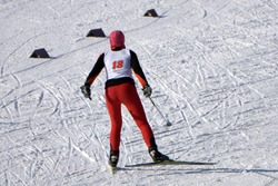 Nordic skier in red in white winter nature full of snow. Sport active photo