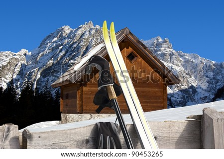Nordic Skiing in the foreground and Wooden chalet in winter - Alps Italy