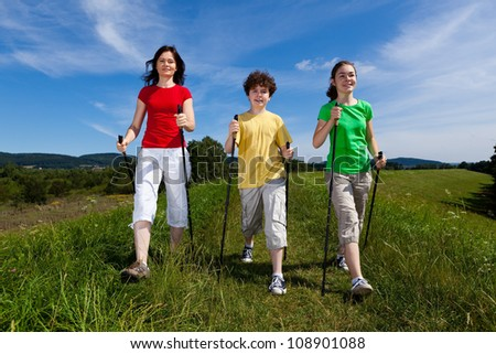 Nordic walking - active family exercising outdoor - stock photo