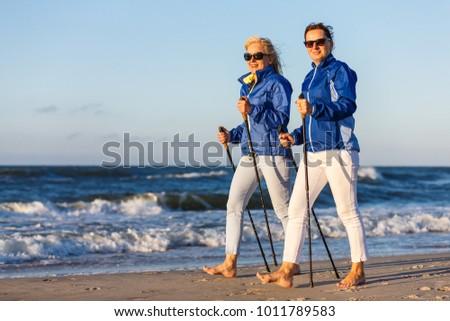 Nordic walking - active people working on beach #1011789583