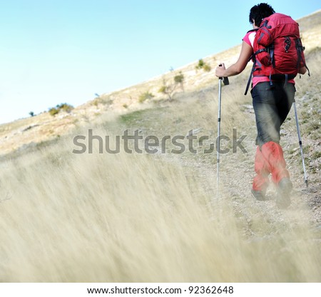 Nordic Walking at mountains, hiking woman in grass