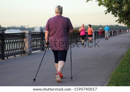Nordic walking, big elderly European woman with ski poles walks in Park alley on a summer day, rear view