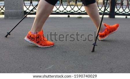 Nordic walking, elderly woman legs in bright orange sneakers with ski poles walks in Park on a summer day, side view close up