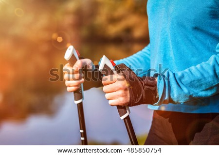 Nordic walking exercise adventure hiking concept - closeup of woman's hand holding nordic walking poles.  With lens flare and light leaks