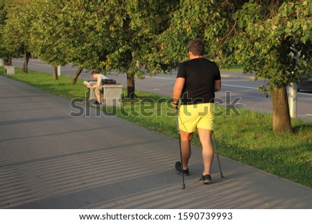 Nordic walking, one man in black t-shirt and yellow shorts with ski poles walks in Park on a summer day, back view against a trees background
