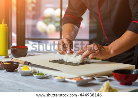 Nori and white rice. Man\'s hands touch rice. Chef starts cooking sushi. Simple recipe of hosomaki rolls.