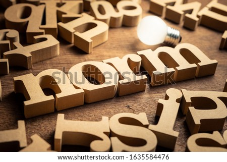 NORM word by wood alphabets with many random letters around and glowing light bulb Photo stock ©