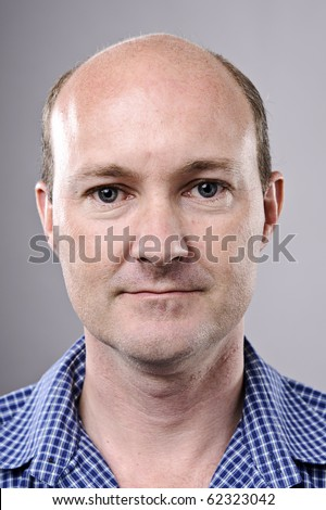 Normal bald man poses for portrait in studio