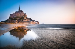 Normandy, France. Le Mont Saint Michel reflecting itself into the sea during sunrise.