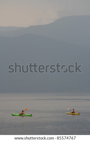 NORRIS POINT, CANADA – JULY 18: Two females kayaking on July 18, 2011 at Norris Point, Newfoundland. Norris Point is surrounded by Gros Morne National Park.