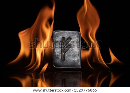Norse rune Fehu. Wealth, creativity, passion, fire. Rune Fehu is associated with the Scandinavian goddess Freya. The rune is isolated in the background of the flames.