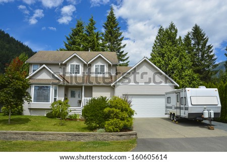 North American family house on country side. Single house with landscaping on the front and blue sky background. RV parked on concrete driveway beside the house