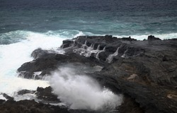North coast of Gran Canaria, lava fields of Banaderos area, grey textured lava from eruption of Montana de Arucas,  stormy weather in October, rockpools separated from the ocean by volcanic rock