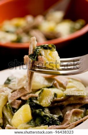 North Italian Regional pasta dish called pizzoccheri on wooden table