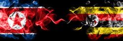 North Korea vs Uganda, Ugandan smoky mystic flags placed side by side. Thick colored silky smoke flags of North Korea and Uganda, Ugandan.