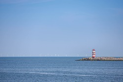 North sea under blue clear sky in summer, Pier IJmuiden with red and white lighthouse tower on the sea side, A port city in the Dutch province of North Holland, Netherlands.