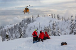 North Vancouver, British Columbia, Canada. North Shore Search and Rescue are rescuing a man skier in the backcountry of Seymour Mountain with a helicopter in winter during sunset.