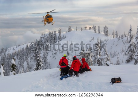 North Vancouver, British Columbia, Canada. North Shore Search and Rescue are rescuing a man skier in the backcountry of Seymour Mountain with a helicopter in winter during sunset. Stock photo ©