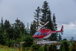 North Vancouver, British Columbia, Canada. Red Helicopter on Top of Grouse Mountain during a colorful summer sunrise.