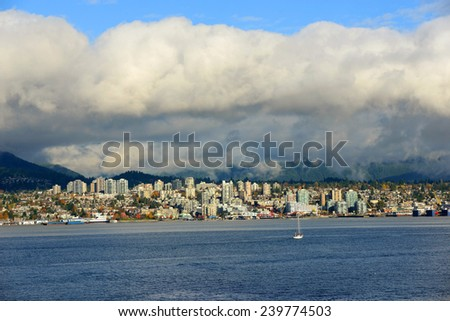 North Vancouver city skyline across Vancouver Harbour in a cloudy day, Vancouver, British Columbia, Canada.