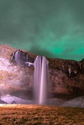 Northen light at Seljalandsfoss waterfall, Iceland.