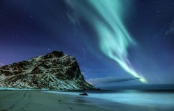 Northen light under mountains and ocean. Beautiful natural landscape in the Norway