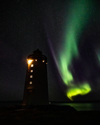 Norther lights aka Aurora borealis on a dark arctic night sky with a flashing lighthouse in a front, Iceland