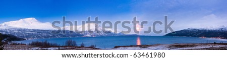 Northern beauty. Panorama. Polar night in Norway. Mountains, fjords, and the moon