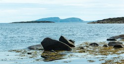Northern calm seascape with rocky shore, boulders and seaweed. Sea islands and harsh northern nature. White Sea, Russia.