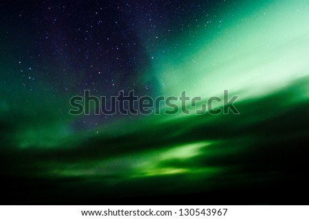 Northern lights above forest and mountain. Captured near Skibon, Norway