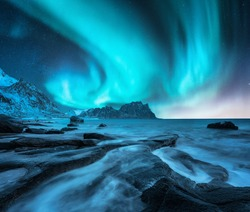 Northern lights above snowy mountains and sandy beach with stones. Aurora borealis in Lofoten islands, Norway. Starry sky with polar lights. Night winter landscape with aurora, sea with blurred water