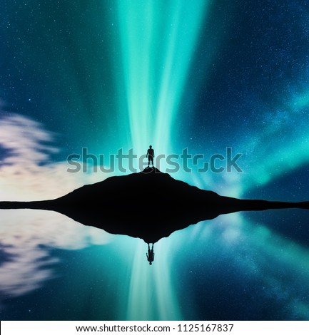 Northern lights and silhouette of standing man in the hill in Norway. Aurora borealis and man. Stars and green polar lights. Night landscape with aurora, lake, sky reflection in water. Travel. Concept #1125167837