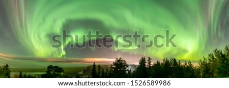 Northern Lights at partly clear skies with thick fog shines above Swedish foggy forest landscape in mountains, green northern lights belt curved above horizon, Northern Sweden, Lappland, copy space Stock foto ©
