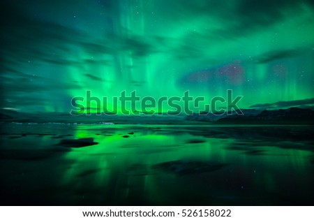 Northern lights (Aurora Borealis) and fast moving clouds reflected over water and icebergs  of glacial lagoon Jokulsarlon in Iceland. #526158022