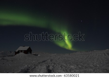 Northern lights (aurora borealis) and night stars of East Greenland winter photographed in minus 40 degrees celsius - stock photo