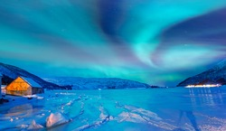Northern lights (Aurora borealis) in the sky over Tromso, Norway - Aurora reflection on the sea on the background Norwegian fjord - Winter season.