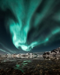 Northern lights, Aurora borealis over amazing landscape in Lofoten, Norway  with mountains in background, Absolutely stunning and beautiful lights on the sky