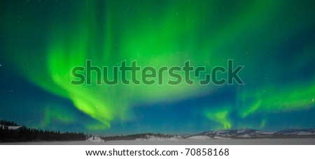 Northern Lights (Aurora borealis) over moon lit snowscape of frozen lake and forested hills.