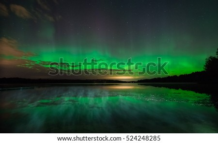 Northern lights (Aurora borealis) reflected over the lake with mist rising over water in the end of summer. Stockholm, Sweden. #524248285