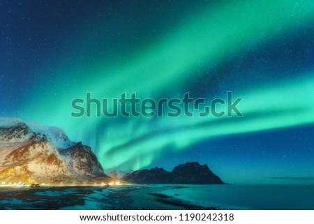Northern lights in Lofoten islands, Norway. Green Aurora borealis. Starry sky with polar lights. Night winter landscape with aurora, sea with sky reflection, rocks, beach and snowy mountains. Nature #1190242318
