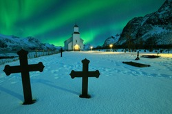 Northern lights over winter landscape with church and graveyard