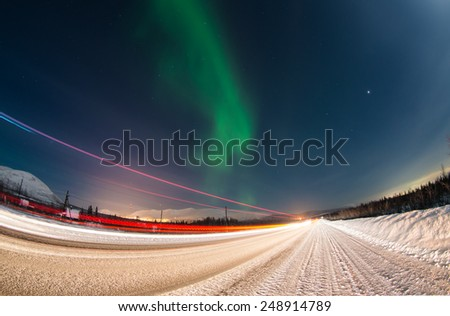 Northern lights over winter road with light trails from moving cars near Apatity town in Murmansk region (Kola peninsula) in northern Russia - long exposure nature background