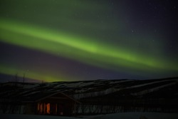 Northern lights with hut, trees and snowy mountains in iceland