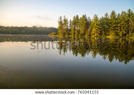 Northern Michigan Wilderness Lake. Wilderness lake with forest reflections in the water and copy space in the foreground in Mio, Michigan.  #765041155