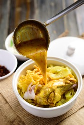 Northern Thai food (Khao Soi), Spicy curry noodles soup with chicken cooking in a bowl